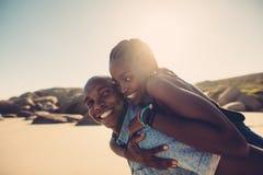 享用在海滩的年轻非洲夫妇 图库摄影