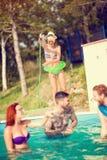 享用在游泳池的小组女性和男性本质上 免版税库存图片