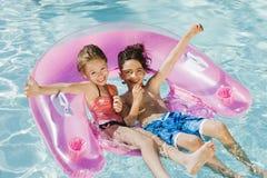 享用在游泳池的朋友 图库摄影