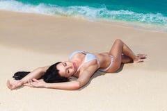 享用在热带海岸的美丽的浅黑肤色的男人太阳 库存照片
