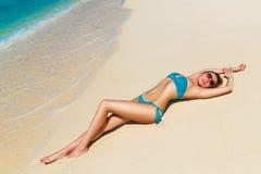 享用在热带海岸的美丽的年轻金发碧眼的女人太阳 免版税图库摄影
