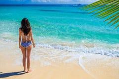 享用在热带海洋的年轻美丽的妇女 华美的g 免版税图库摄影