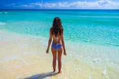 享用在热带海洋的年轻美丽的妇女 华美的g 免版税库存图片