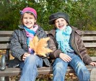 享用在秋天的愉快的女孩和男孩画象  库存图片