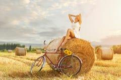 享用在秸杆大包的美丽的妇女太阳,在老红色自行车旁边 免版税库存照片