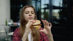 享用在街道城市咖啡馆的女孩的特写镜头一个新鲜的汉堡包 影视素材