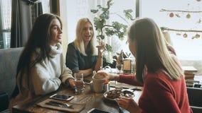 享用在谈话的四个女性朋友在咖啡馆 股票录像