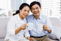 享用在长沙发的夫妇Potrait咖啡 库存照片