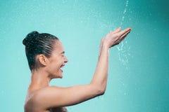享用在阵雨的妇女水在喷气机下 图库摄影
