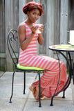 享用在露台的年轻黑人妇女咖啡 免版税图库摄影