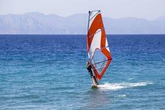 享用在风帆冲浪的女孩 库存照片