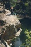 享用在高峭壁的妇女蓝色湖水在夏天 图库摄影