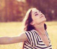 享用在晴朗的夏日wi的自由松弛妇女新鲜空气 免版税图库摄影