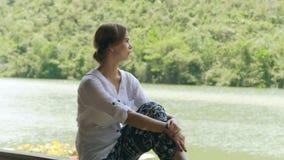 享用夏天河和山的女孩盖了绿色看起来森林的少妇放松在湖岸和绿色 股票视频