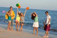 享用夏天海滩的青年人集会,跳舞。 免版税库存图片