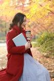 享用外带的咖啡杯的匿名妇女在晴朗的冷的秋天天坐在树下 库存图片