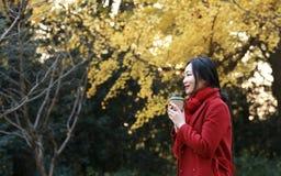 享用外带的咖啡杯的匿名妇女在晴朗的冷的秋天天坐在树下 免版税库存照片