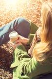 享用外带的咖啡杯的匿名妇女在晴朗的冷的秋天天 库存照片
