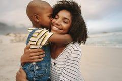 享用天的男孩与他的海滩的母亲 免版税库存图片