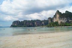 享用天空蔚蓝和绿松石海滩与岩石的人们在甲米府,泰国 免版税库存照片