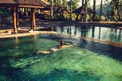 享用太阳的妇女在无限夏天游泳池在豪华手段和温泉旅馆 图库摄影