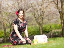 享用太阳的美丽的女孩在一顿野餐期间在春天 图库摄影