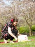享用太阳的美丽的女孩在一顿野餐期间在春天 库存图片