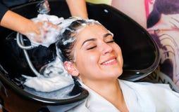 享用头发的美丽的女孩洗涤在理发沙龙 免版税库存照片