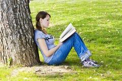 享用女孩年轻人的书 免版税库存照片