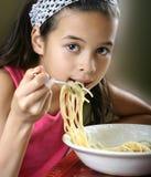 享用女孩意大利面食年轻人的碗 图库摄影