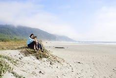 享用女孩的海滩二个年轻人 免版税图库摄影