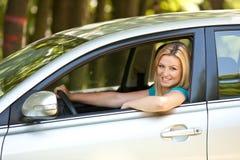 享用女孩的美丽的汽车她新 库存照片