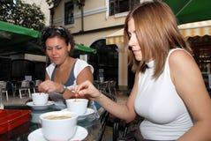 享用女性朋友的coffe杯子 库存图片