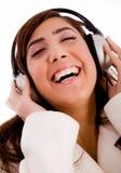 享用女性音乐纵向微笑的年轻人 免版税库存图片