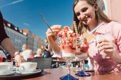 享用她的冰用草莓的妇女 免版税库存照片