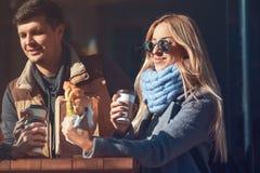 享用她的午餐新月形面包用咖啡的美丽的少妇,当站立户外咖啡馆的她和与朋友时沟通 免版税库存图片
