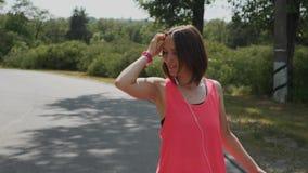 享用她的可爱的嬉戏女孩走在公园 耳机跳舞的年轻女人 桃红色衬衣微笑的逗人喜爱的女孩 Beautif 股票录像