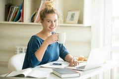享用她的咖啡的办公室妇女画象 免版税库存图片