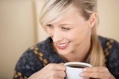 享用她的咖啡的可爱的白肤金发的妇女 免版税库存照片