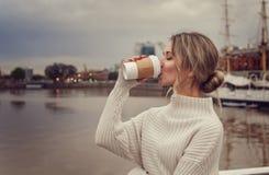享用她的咖啡的少妇户外 免版税库存图片