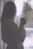 享用她的早晨咖啡的妇女 库存照片