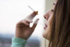 享用她的香烟的妇女 免版税库存图片
