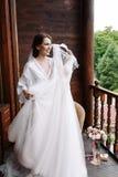 享用婚礼礼服的华美,愉快的微笑新娘在佩带前 早晨准备 投入在礼服的妇女 免版税库存照片