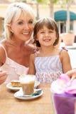 享用孙女祖母的咖啡 免版税库存照片