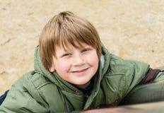 享用室外操场的白肤金发的男孩 免版税库存图片