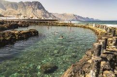 享用岩石水池的游人在Puerto de在大加那利岛的las Nieves 免版税库存图片