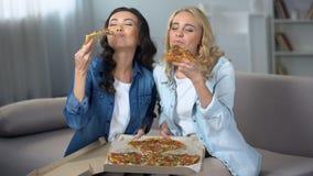 享用巨大的可口比萨的两饥饿的女生户内,食物交付 股票录像