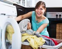 享用干净的衣裳的妇女在洗衣店以后 库存图片