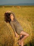 享用干草倾斜的栈妇女年轻人的微风 图库摄影