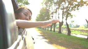 享用年轻亚裔的妇女感觉风通过车窗 股票视频